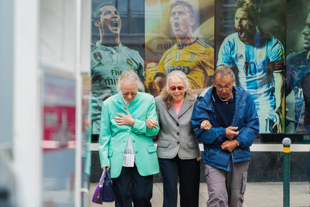 Tiga warga Jenewa, Swiss, yang difoto di dekat halte dengan foto pemain sepak bola dunia seperti Cristiano Ronaldo, Paulo Dybala, dan Lionel Messi.